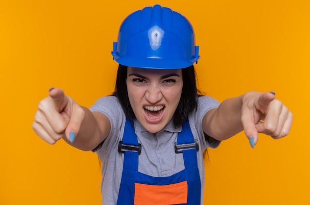 建設制服と安全ヘルメットポインティングの若いビルダーの女性