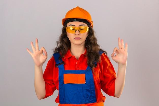 建設制服と安全ヘルメットの若いビルダー女性リラックスして目を笑顔で孤立した白い壁に指で瞑想ジェスチャーをして閉じた