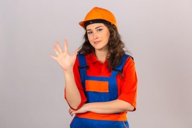 建設制服と安全ヘルメットの若いビルダー女性笑顔陽気な表示と分離された白い壁を越えて自信と幸せを探して指番号5を指して上向き
