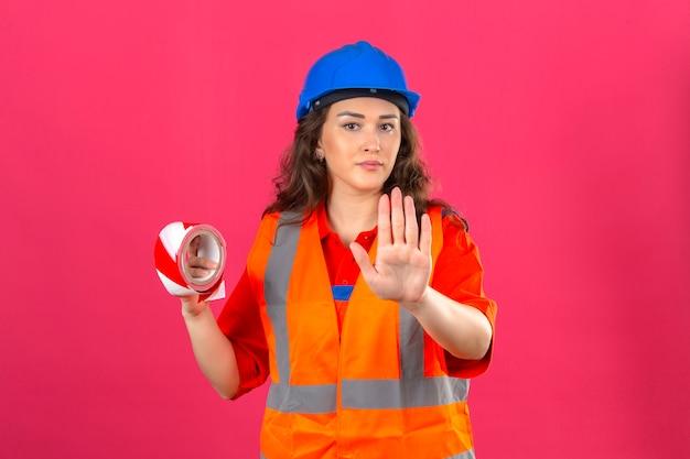 Молодая женщина строитель в строительной форме и защитный шлем, стоя с клейкой лентой и делая жест остановки с другой стороны над изолированной розовой стеной