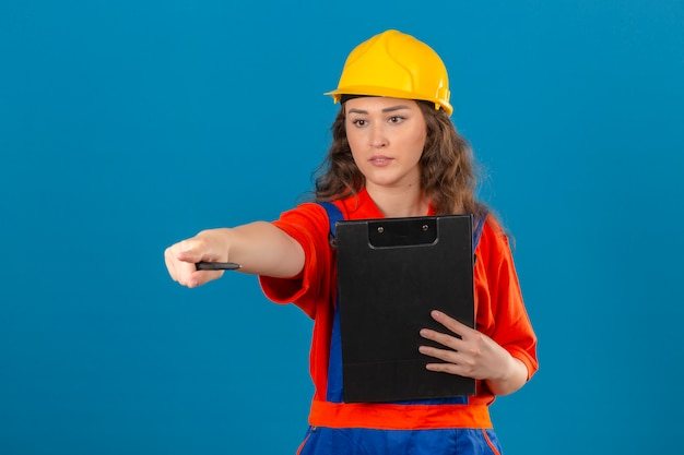 クリップボードで立っている制服と安全ヘルメットの若いビルダー女性と孤立した青い壁に人差し指で何かを指しています。