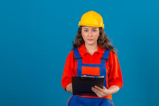 孤立した青い壁に深刻な顔をして手でクリップボードで建設の制服と安全ヘルメット立っている若いビルダー女性