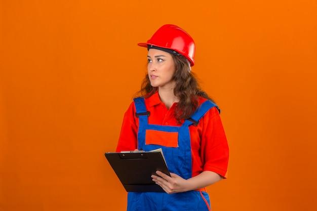 孤立したオレンジ色の壁を見渡してクリップボードで建設の制服と安全ヘルメット立っている若いビルダー女性