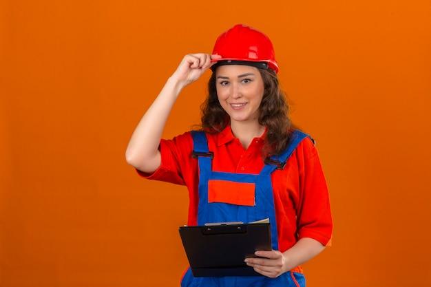 孤立したオレンジ色の壁を越えて彼女のヘルメットに触れるフレンドリーな笑みを浮かべてクリップボードで建設の制服と安全ヘルメット立っている若いビルダー女性