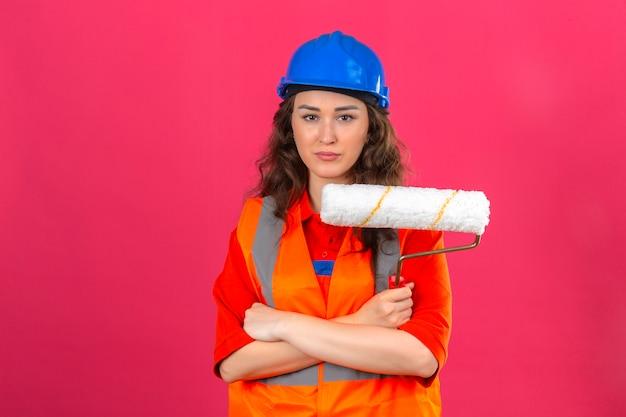 孤立したピンクの壁に深刻な顔でペイントローラーを保持している組んだ腕と建設の制服と安全ヘルメット立っている若いビルダー女性