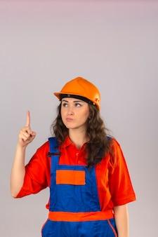 Молодая женщина строитель в строительной форме и защитный шлем, стоя с пальцем вверх предупреждение об опасности над изолированной белой стеной