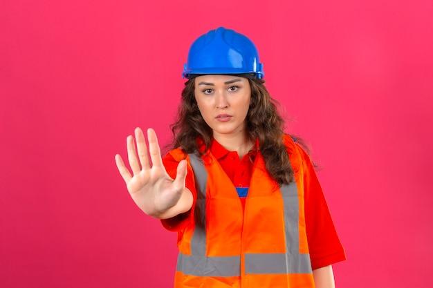 Молодая женщина строитель в строительной форме и защитный шлем, стоя с открытой руки, делая знак остановки с серьезным и уверенным выражением защиты жест над изолированной розовой стеной