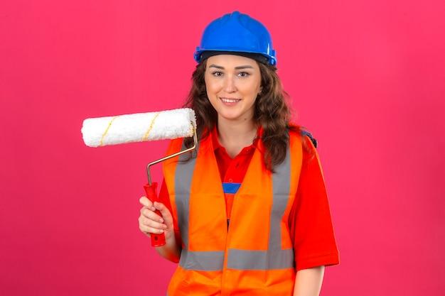 孤立したピンクの壁を越えてカメラで顔に笑顔を見てペイントローラーで建設の制服と安全ヘルメット立っている若いビルダー女性