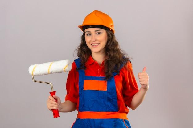 建設の制服と安全ヘルメット立っている若いビルダー女性ペイントローラー笑顔で孤立した白い壁の上に親指を表示笑みを浮かべて