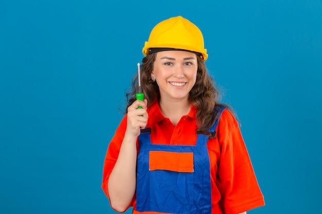Молодая женщина строитель в строительной форме и защитный шлем, стоя с отверткой, улыбаясь дружественных над синей стеной