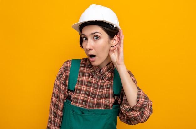 Молодая женщина-строитель в строительной форме и защитном шлеме удивлена, держась за ухо, пытаясь слушать сплетни, стоя на оранжевом