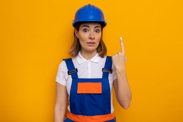 オレンジ色の壁の上に立っているナンバーワンの人差し指を示して驚いた建設制服と安全ヘルメットの若いビルダーの女性