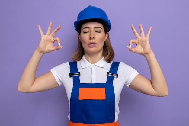 紫色の壁の上に立って目を閉じて指で瞑想ジェスチャーを作ってリラックスしようとしている建設制服と安全ヘルメットの若いビルダーの女性