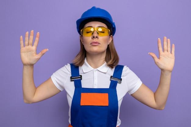 건설 유니폼을 입은 젊은 건축업자 여성과 안전 노란색을 입은 안전 헬멧을 쓴 눈을 감고 보라색 위에 서 있는 팔 안경을 들고