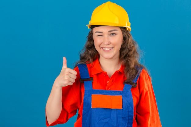 Молодой строитель женщина в строительной форме и защитный шлем, подмигивая показывает палец вверх с счастливым лицом на изолированной синей стене