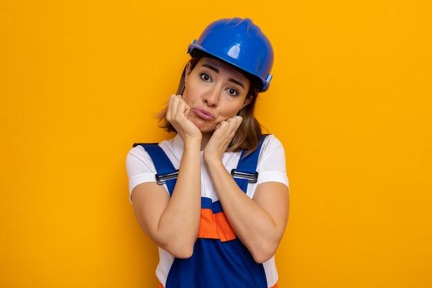 オレンジ色の上に立っている唇をすぼめる顔に悲しい表情で建設制服と安全ヘルメットの若いビルダーの女性