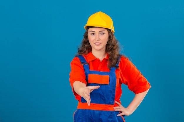 Молодая женщина строитель в строительной форме и защитный шлем с улыбкой, предлагая рукой сделать жест приветствия над синей стеной