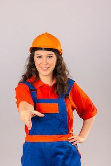 Молодая женщина строитель в строительной форме и защитный шлем с улыбкой, предлагая руку, делая приветствие жест над изолированной белой стене