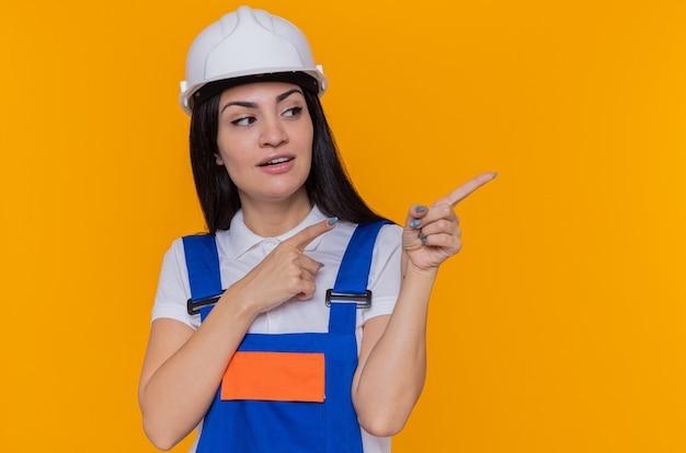 Молодая женщина-строитель в строительной форме и защитном шлеме