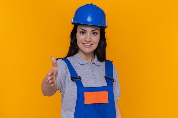 건설 유니폼과 안전 헬멧에 젊은 작성기 여자