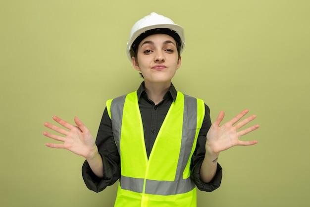 建設ベストと安全ヘルメットの若いビルダーの女性は、緑の上に立っている側に腕を広げて混乱しました