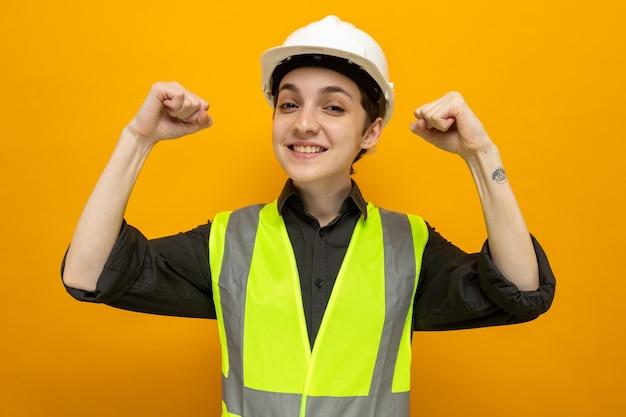 건설 조끼와 안전 헬멧을 쓴 젊은 건축업자 여성은 주황색 벽 위에 서 있는 승자처럼 행복하고 흥분된 주먹을 들고 있다