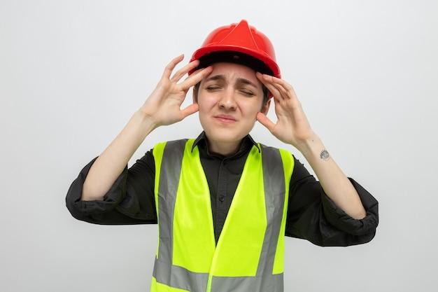 頭痛に苦しんでいる彼女の頭に触れて体調を崩しているように見える建設ベストと安全ヘルメットの若いビルダーの女性