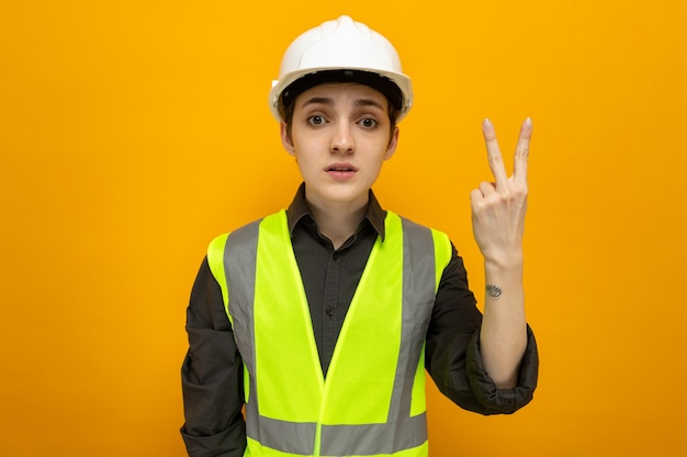 建設ベストと安全ヘルメットの若いビルダーの女性は、指で2番目を示す深刻な顔で見ています
