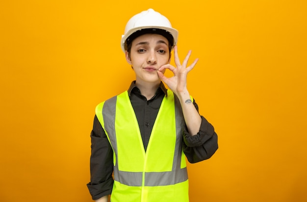 オレンジ色の上に立っているジッパーで口を閉じるような沈黙のジェスチャーを作る建設ベストと安全ヘルメットの若いビルダーの女性