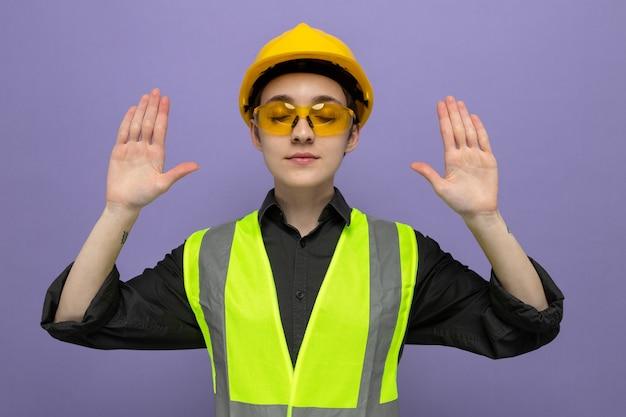 安全黄色のメガネを身に着けている建設ベストと安全ヘルメットの若いビルダーの女性は幸せで前向きな腕を上げる