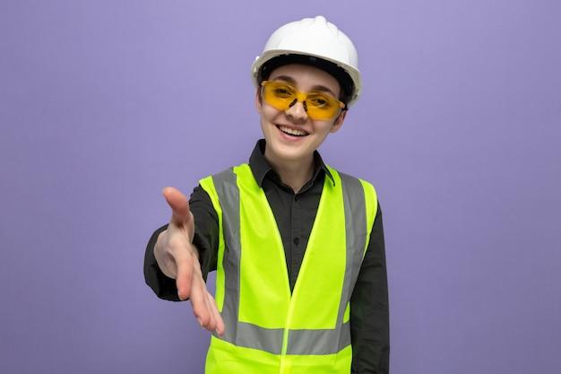 建設ベストと安全ヘルメットを身に着けている若いビルダーの女性は、青い壁の上に立っている手の挨拶のジェスチャーを提供するフレンドリーな笑顔の安全黄色の眼鏡をかけています