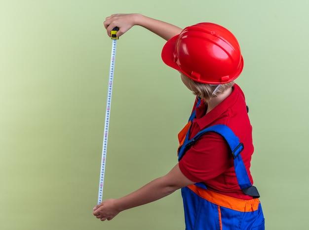 Giovane donna del costruttore in uniforme che allunga il metro a nastro isolato sulla parete verde oliva