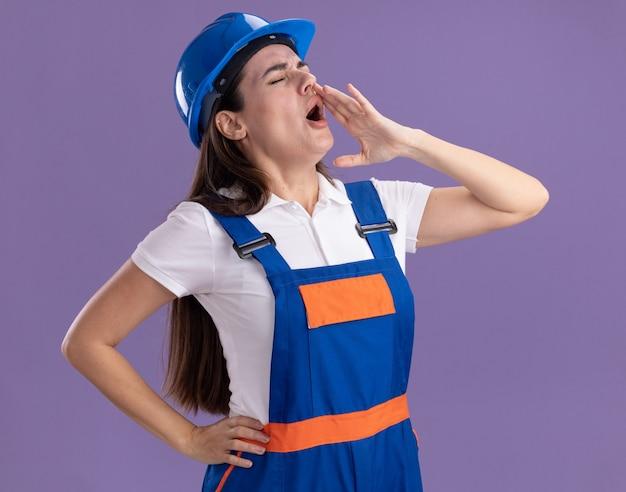 Молодая женщина-строитель с закрытыми глазами в униформе зовет кого-то изолированного на фиолетовой стене