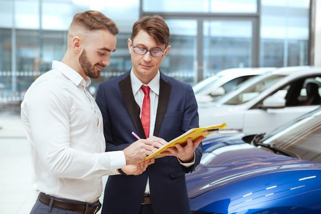 Молодой бизнесмен покупает новый автомобиль