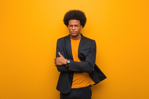 Young business african american man over an orange wall crossing arms relaxed