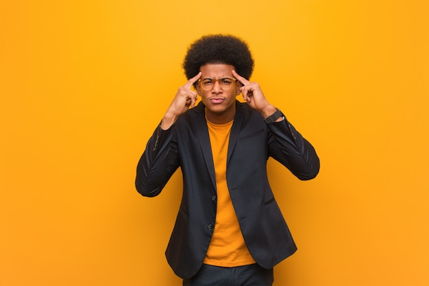 Young business african american man over an orange wall doing a concentration gesture