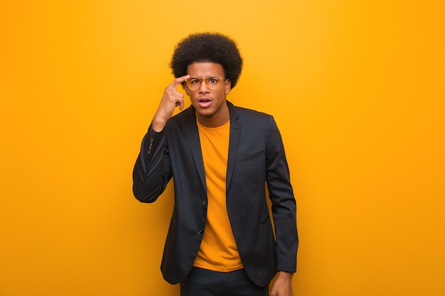 Young business african american man on an orange wall doing a disappointment gesture with finger