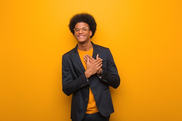 Young business african american man on an orange wall doing a romantic gesture
