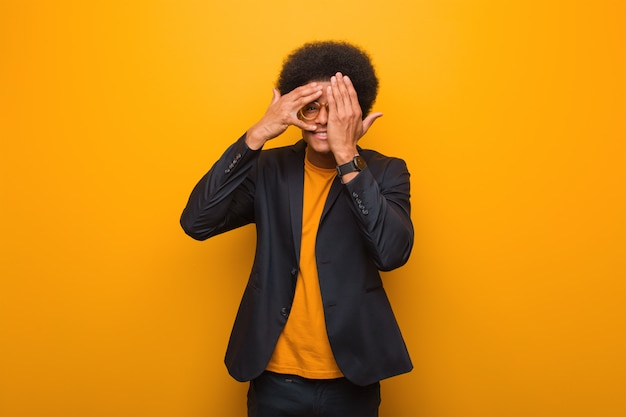 Young business african american man over an orange wall feels worried and scared