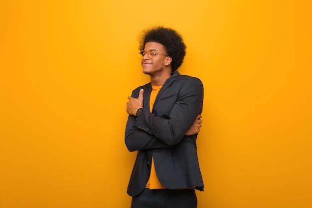 Young business african american man on an orange wall giving a hug
