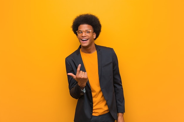 Young business african american man over an orange wall inviting to come