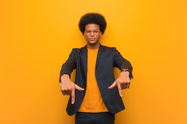 Young business african american man over an orange wall pointing to the bottom with fingers