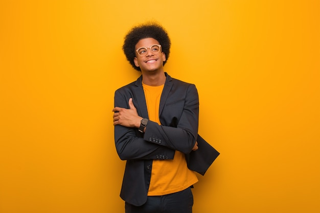 Young business african american man over an orange wall smiling confident and crossing arms, looking up