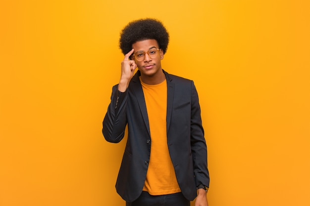 Young business african american man over an orange wall thinking about an idea