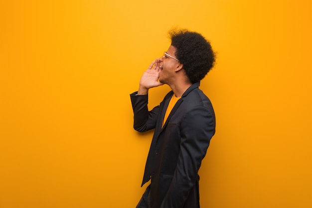 Young business african american man over an orange wall whispering gossip undertone