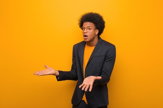 Молодой деловой афроамериканец над оранжевой стеной в замешательстве и сомнении