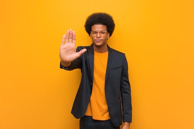 Молодой деловой афро-американский мужчина над оранжевой стеной, положив руку вперед