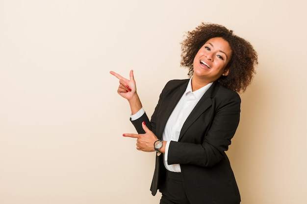 Young business african american woman excited pointing with forefingers away.