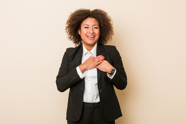 Young business african american woman has friendly expression, pressing palm to chest. love concept.