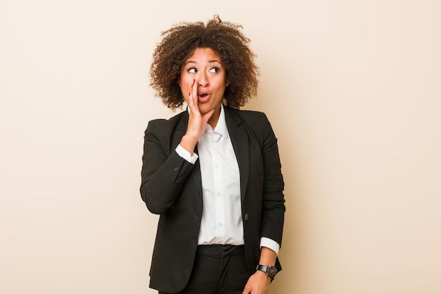 若いビジネスアフリカ系アメリカ人女性は秘密のホットブレーキニュースを言って、よそ見